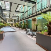 New atrium walkways provide access for the hotel apartment, condominium, courtyard, interior design, mixed use, plant, property, real estate, gray
