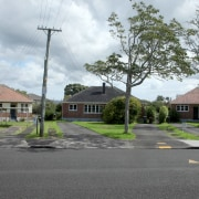 The land these three old war-era duplexes used area, asphalt, estate, home, house, land lot, landscape, neighbourhood, property, real estate, residential area, road, road surface, roof, sky, suburb, town, tree, gray, white