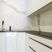 Sleek cabinet finishes seen in the kitchen are architecture, countertop, floor, interior design, kitchen, product design, property, tap, wall, white