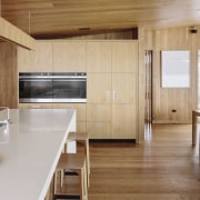 This contemporary kitchen is central to proceedings, positioned architecture, cabinetry, countertop, floor, flooring, hardwood, house, interior design, kitchen, laminate flooring, real estate, wood, wood flooring, brown, gray, orange