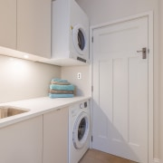 The washer and wall-mounted dryer in this laundry clothes dryer, home appliance, kitchen, laundry, laundry room, major appliance, property, real estate, room, washing machine, gray