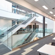 The three-storey atrium, or Learning Laneway, in Te architecture, condominium, daylighting, glass, handrail, interior design, real estate, stairs, white, gray