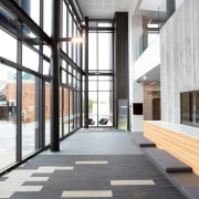 The double-height entry plaza shows how external cladding architecture, building, daylighting, floor, flooring, interior design, lobby, structure, window, wood flooring, white, gray