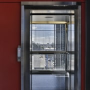 An external elevator with a stainless steel and architecture, door, facade, glass, window, red, gray