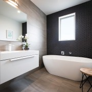 This contemporary GJ Gardner-designed bathroom includes a hexagon bathroom, floor, home, interior design, product design, room, sink, gray, black
