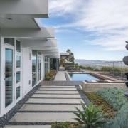 A new pool and landscaping runs the length apartment, architecture, condominium, estate, home, house, property, real estate, gray, white