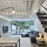 The length of this basement is accentuated by architecture, ceiling, condominium, daylighting, house, interior design, living room, lobby, real estate, gray
