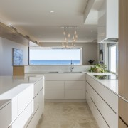 This crisp white and wood kitchen part of cabinetry, countertop, ceasarstone, benchtop, travertine floor, kitchen, Craig Steere