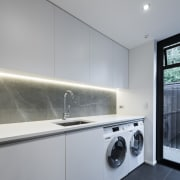 This spacious laundry is served by a walk-in architecture, countertop, home appliance, interior design, kitchen, laundry, laundry room, major appliance, room, gray