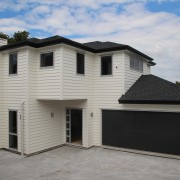 One of two houses built by a Remuera building, elevation, estate, facade, home, house, property, real estate, residential area, roof, siding, gray