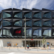 High-profile brand H&M literally has a high-profile facade architecture, building, commercial building, mixed use, structure, gray, black