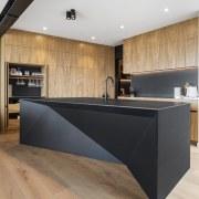 The perimeter natural wood veneer cabinetry tones with