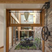 The central courtyard is accessed through vertically hung beam, home, house, interior design, real estate, window, brown, gray