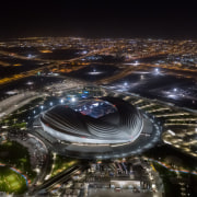 The dramatic Al Janoub Stadium by night. - aerial photography, architecture, arena, bird's-eye view, city, cityscape, human settlement, landscape, metropolis, metropolitan area, night, photography, sky, skyscraper, soccer-specific stadium, space, sport venue, stadium, urban area, water, black