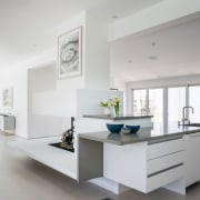 The kitchen benchtop waterfalls downwards and round the