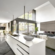 The home's centrally located crisp white kitchen overlooks