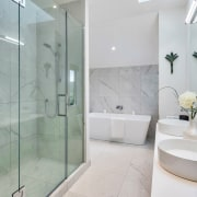 The modern master bathroom features table top basins,