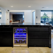 The built-in wine fridge presents as a colourful architecture, building, cabinetry, ceiling, countertop, desk, floor, flooring, furniture, home, house, interior design, kitchen, lighting, living room, property, real estate, room, table, tile, gray, black