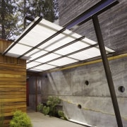 A translucent awning contrasts the solid mass of architecture, daylighting, house, roof, gray, black