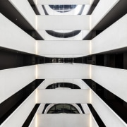 The dramatic residential lobby is decorated with reference architecture, black-and-white, building, commercial building, daylighting, design, facade, line, mixed-use, monochrome, parallel, pattern, sky, symmetry, white, white, black, atrium