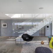 The first floor of this beachhouse accommodates a apartment, architecture, ceiling, daylighting, floor, house, interior design, living room, lobby, real estate, gray