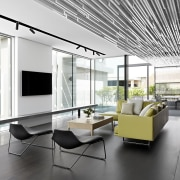 The informal living area opens out to an architecture, ceiling, floor, house, interior design, living room, lobby, office, white, gray