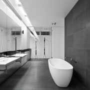 This bathroom features a mirrored wall with a architecture, bathroom, black and white, daylighting, floor, interior design, monochrome, monochrome photography, plumbing fixture, room, tile, gray, black