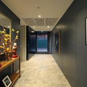 A deliberately compressed hallway makes the arrival into boutique, ceiling, interior design, lobby, room, black, brown