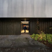 Positioned in a side lane, the front door architecture, facade, home, house, property, real estate, black, gray