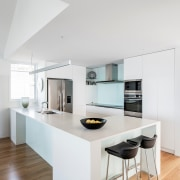 The seaside home's white kitchen merges with the