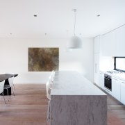 This kitchen with prominent island bench forms part architecture, building, ceiling, concrete, daylighting, design, floor, flooring, furniture, hardwood, home, house, interior design, kitchen, line, living room, loft, material property, property, room, space, table, tile, wall, white, wood, wood flooring, white, gray