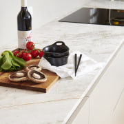 Classic material – granite – meets contemporary slender countertop, cuisine, cutting board, dish, food, furniture, interior design, kitchen, room, table, tile, wood, white