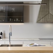 A long slender pendant contrasts the solidity of cabinetry, countertop, cupboard, floor, flooring, furniture, house, interior design, kitchen, material property, property, room, shelf, sink, tap, tile, white, gray