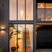 The focal point of this renovated home's front architecture, auto part, automotive exterior, building, door, facade, furniture, glass, home, house, interior design, material property, real estate, room, tree, vehicle door, window, black, orange