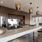 Three large pendants' have been used to support architecture, building, cabinetry, ceiling, countertop, cuisine classique, design, floor, flooring, furniture, granite, hardwood, home, house, interior design, kitchen, loft, property, real estate, room, table, tile, wood, wood flooring, gray
