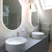 The floating vanity is underlit to accentuate the