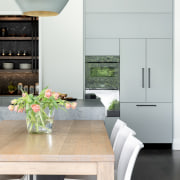 The wall ovens provide reflective counterpoints to the