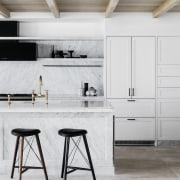 Black detailing complements the pale, veined stone surfaces