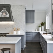 The demure grey cabinetry flows through from front
