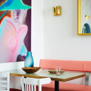 The colour scheme is big and camp, with chair, furniture, home, interior design, lampshade, lighting accessory, living room, pink, room, table, wall, white