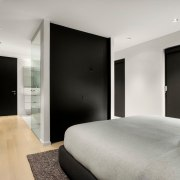 A strong black and white theme runs through apartment, architecture, bed, bed frame, bed sheet, bedroom, black-and-white, boutique hotel, building, ceiling, design, floor, furniture, home, house, interior design, laminate flooring, monochrome photography, property, real estate, room, suite, table, wall, wood flooring, gray, black