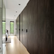 A long line of dark timber coloured cabinetry architecture, building, ceiling, concrete, design, floor, flooring, furniture, hall, hardwood, home, house, interior design, loft, plywood, property, room, space, wall, wood, wood flooring, gray, black