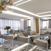 The living area is a big open space, apartment, building, ceiling, dining room, floor, furniture, home, house, interior design, living room, property, real estate, restaurant, room, suite, table, gray