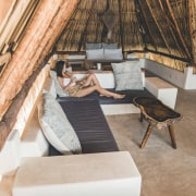 The locally inspired thatched palm roof dominating the comfort, floor, furniture, house, interior design, leg, leisure, room, table, tree, vacation, gray