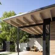 The extended roof shelters the outdoor room at