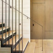 Only a tell-tale latch acknowledges the presence of architecture, door, floor, flooring, furniture, glass, handrail, interior design, iron, line, metal, room, stairs, wood, orange, white