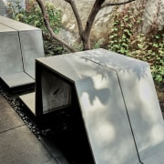 Linear furniture, stretched out like a ribbon along architecture, concrete, plant, sculpture, tree, wall, gray, black
