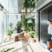 The elevator trough which visitors enter the building architecture, balcony, building, daylighting, door, facade, flowerpot, glass, home, house, houseplant, interior design, plant, property, real estate, room, window, white