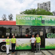 "The Singapore green-roofed 10-bus initiative  is called ""Gardens advertising, architecture, bus, car, commercial vehicle, mode of transport, motor vehicle, tour bus service, tourism, transport, tree, vehicle, gray, black, white"