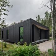 Darkened wooden slats clad the other three façades